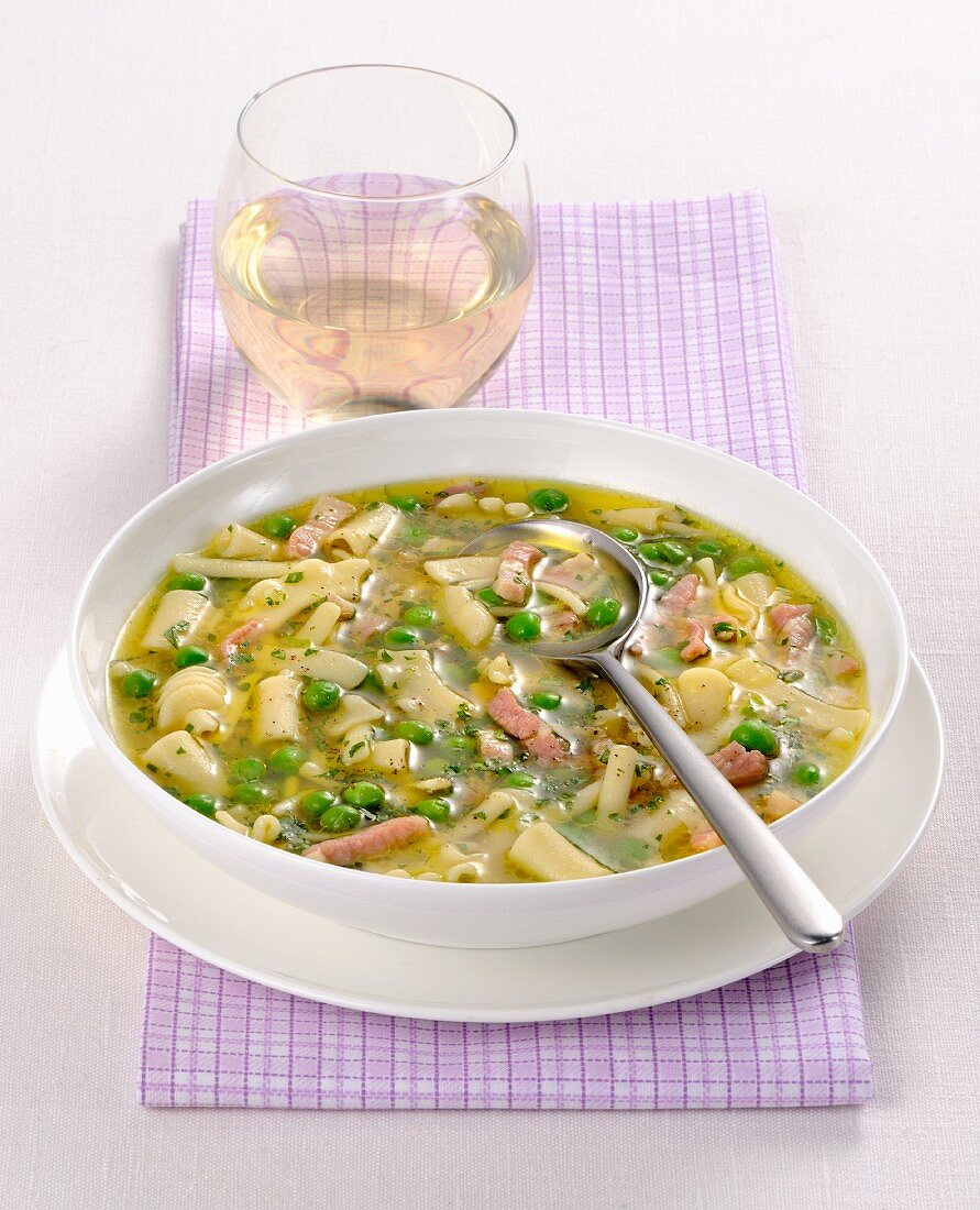 Noodle soup with peas and strips of ham