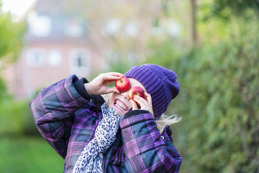 A little girl wearing winter clothing covering her eyes with two apples