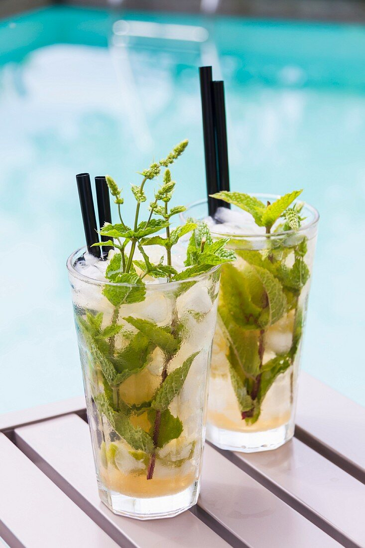 Two Mojitos on a table by a pool