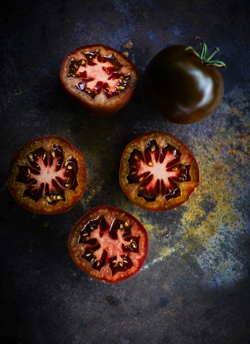 Schwarze Tomaten, ganz und halbiert (Aufsicht)