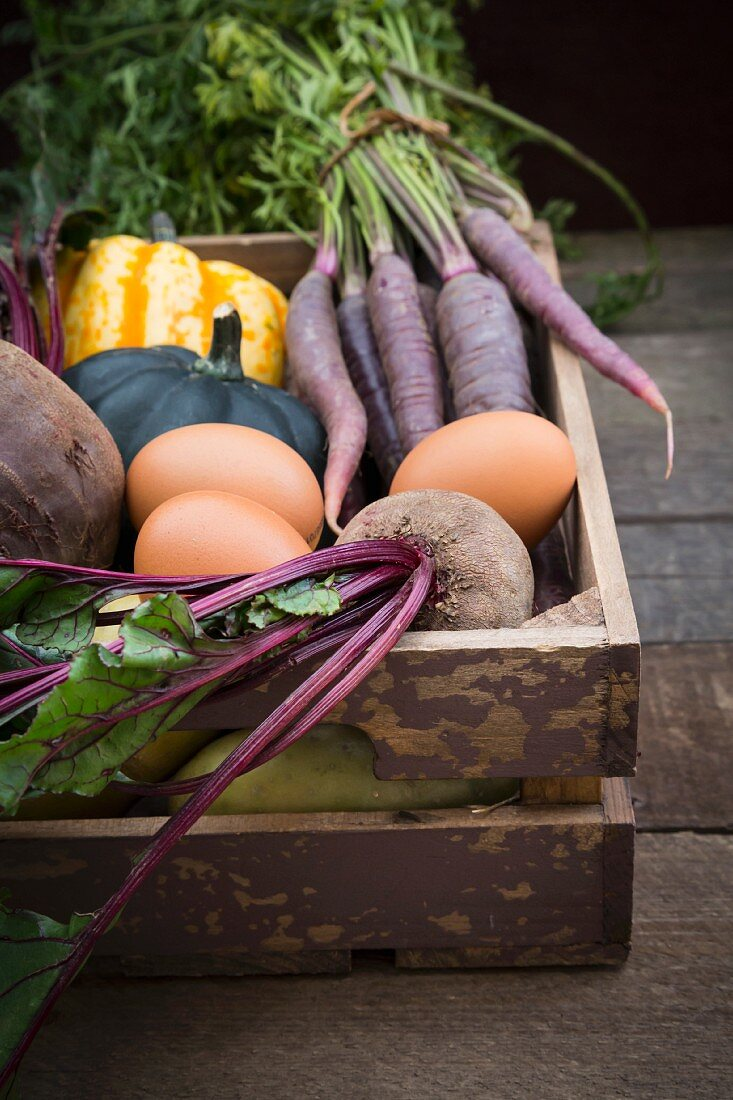 Various organic vegetables and eggs in a wooden crate