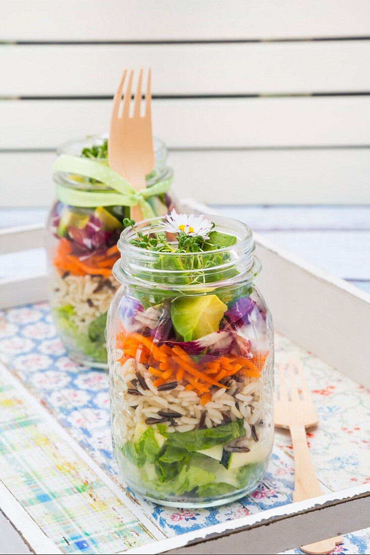 Layered spring salads with rice, vegetables and daisies in jars on a tray