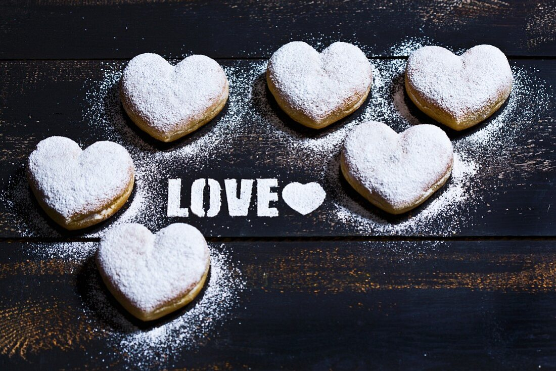 The word Love stencilled with icing sugar and surrounded by heart-shaped doughnuts