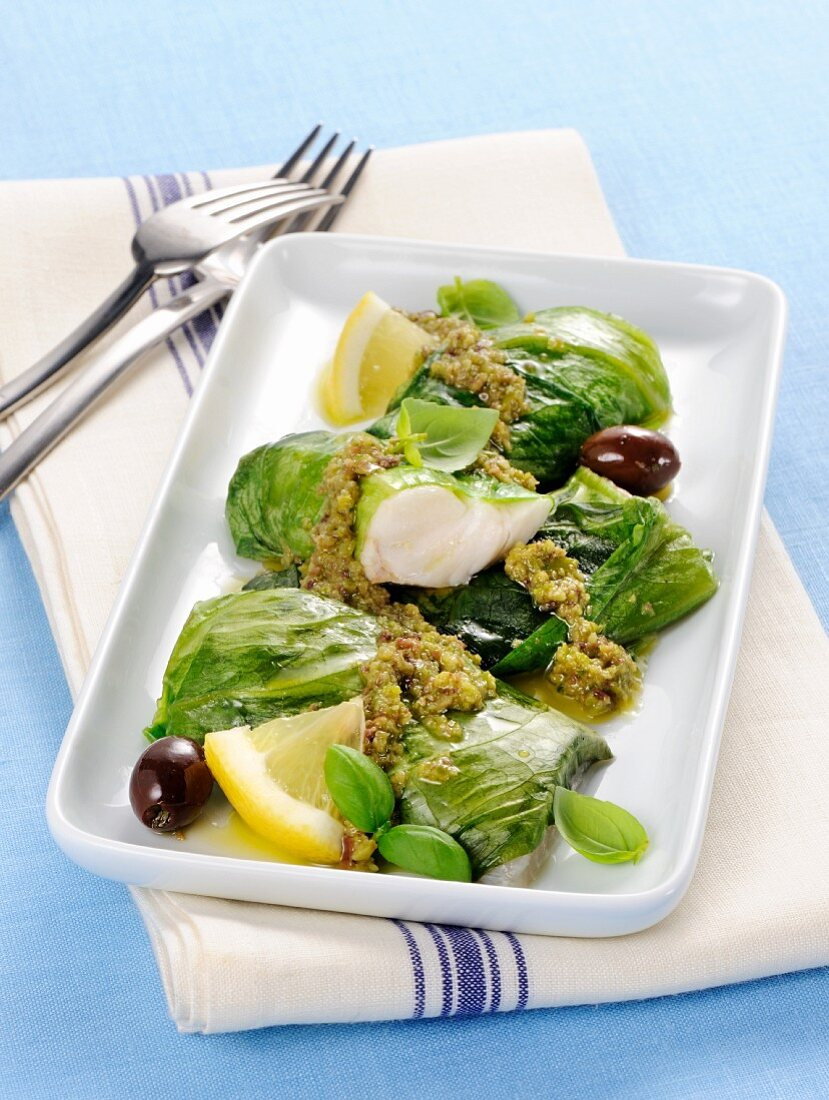 Hake and lettuce rolls with a green olive sauce and lemons
