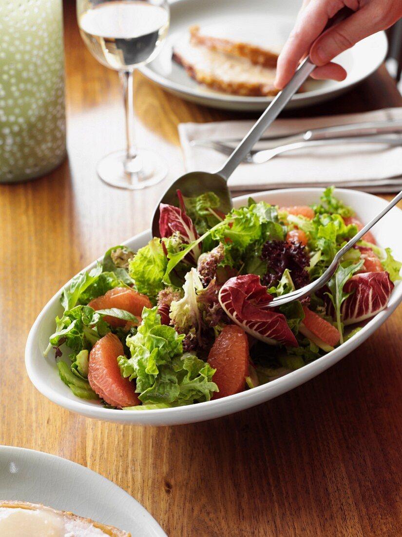 Mixing Leafy Grapefruit & Celery Salad