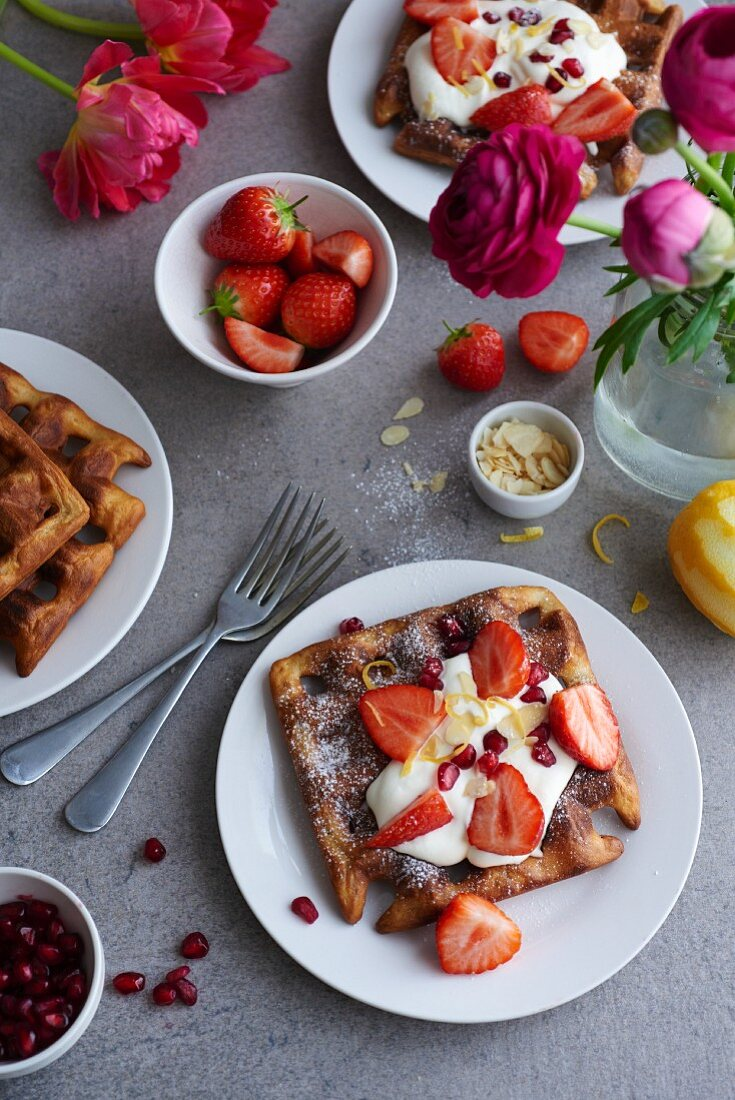 Waffles with cream, strawberries and pomegranate seeds