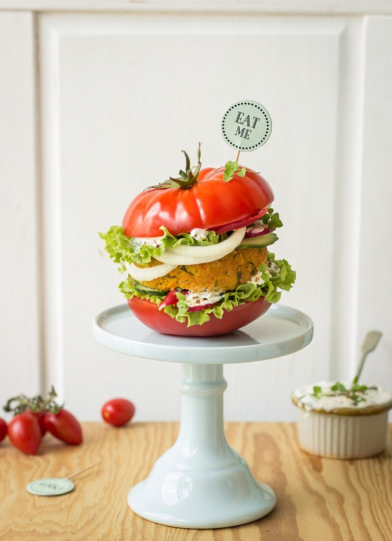 A carrot and chickpea burger in a tomato 'bun'