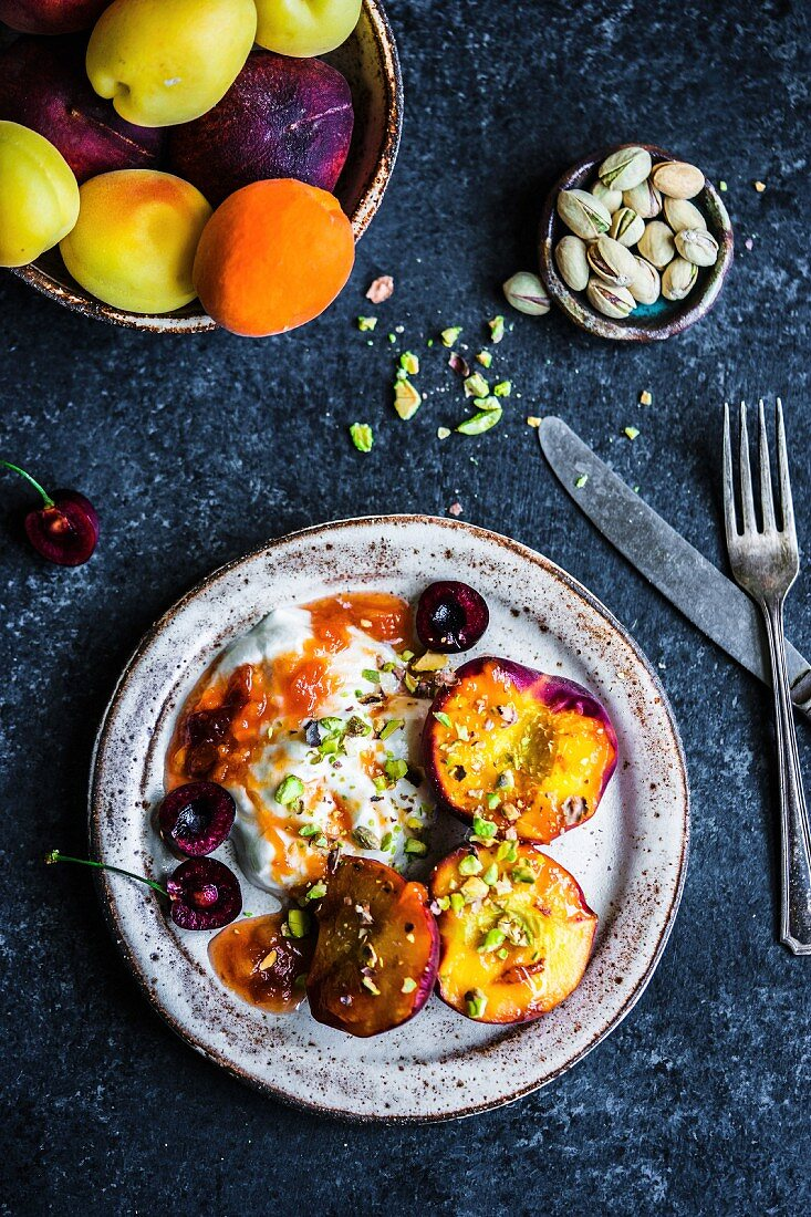 Grilled peaches with coconut yogurt, apricot jam and pistachios