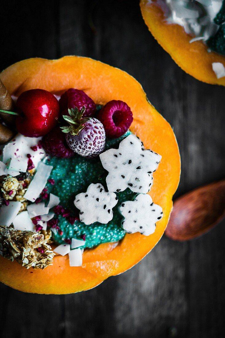 Melon bowl with muesli, coconut yogurt, chia spirulina pudding, dragon fruit flowers and berries