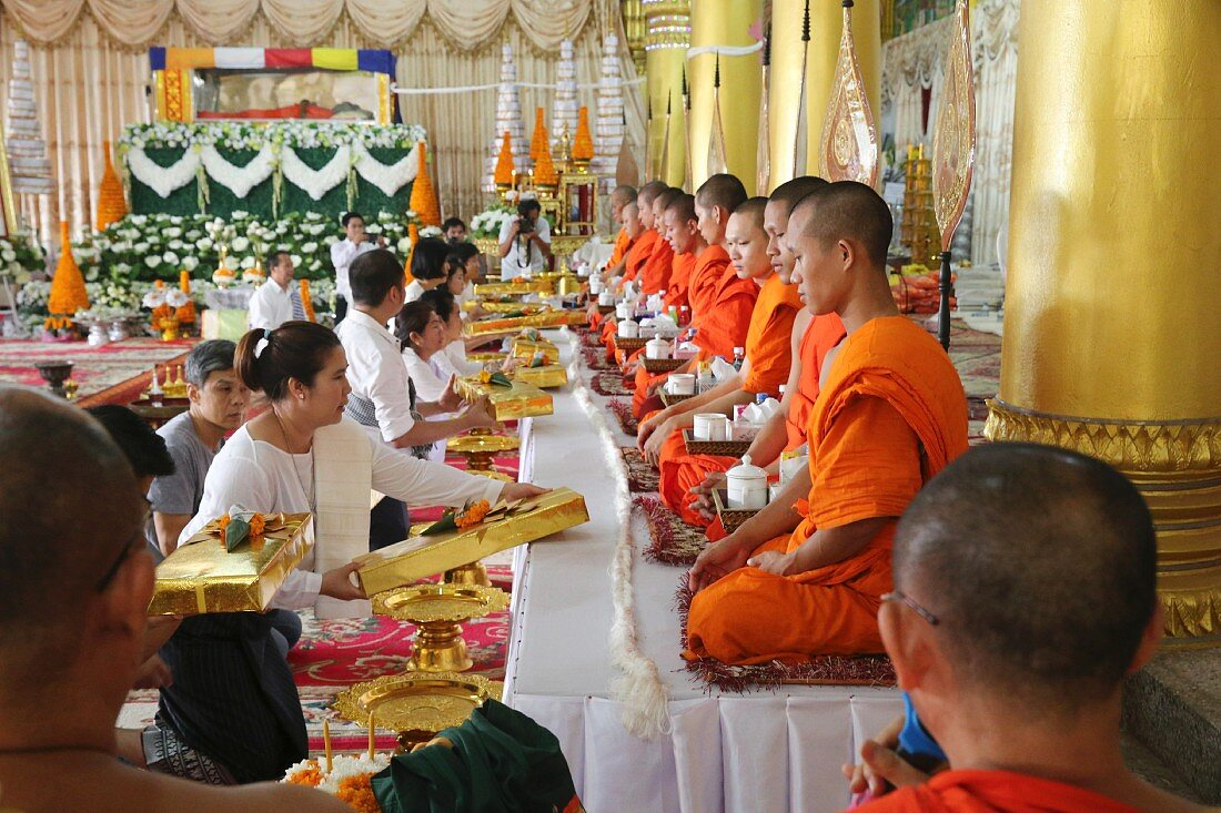 Monk sitting at a ceremony in the Wat Ong Teu Buddhist temple, Vientiane, Laos
