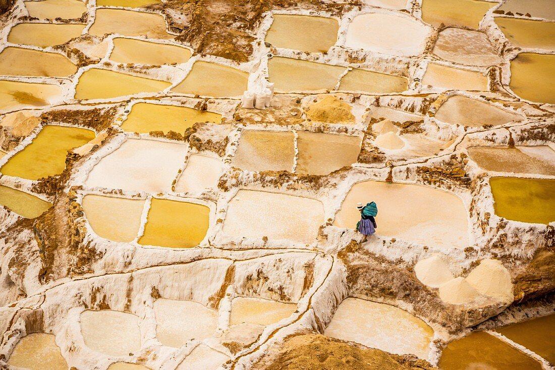 A woman harvesting salt in the salt pans of Maras, Sacred Valley, Peru, South America