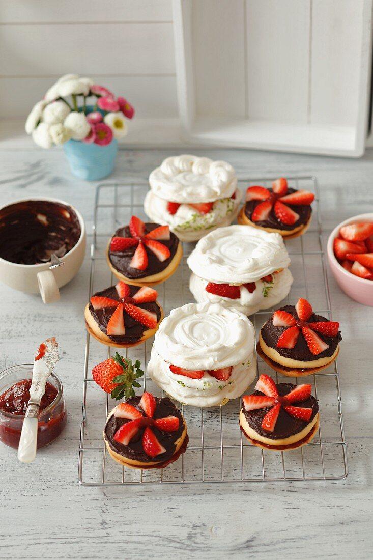 Schokoladen-Doppelkekse mit Erdbeermarmelade und Mini-Pavlovas mit Limetten-Schlagsahne und Erdbeeren