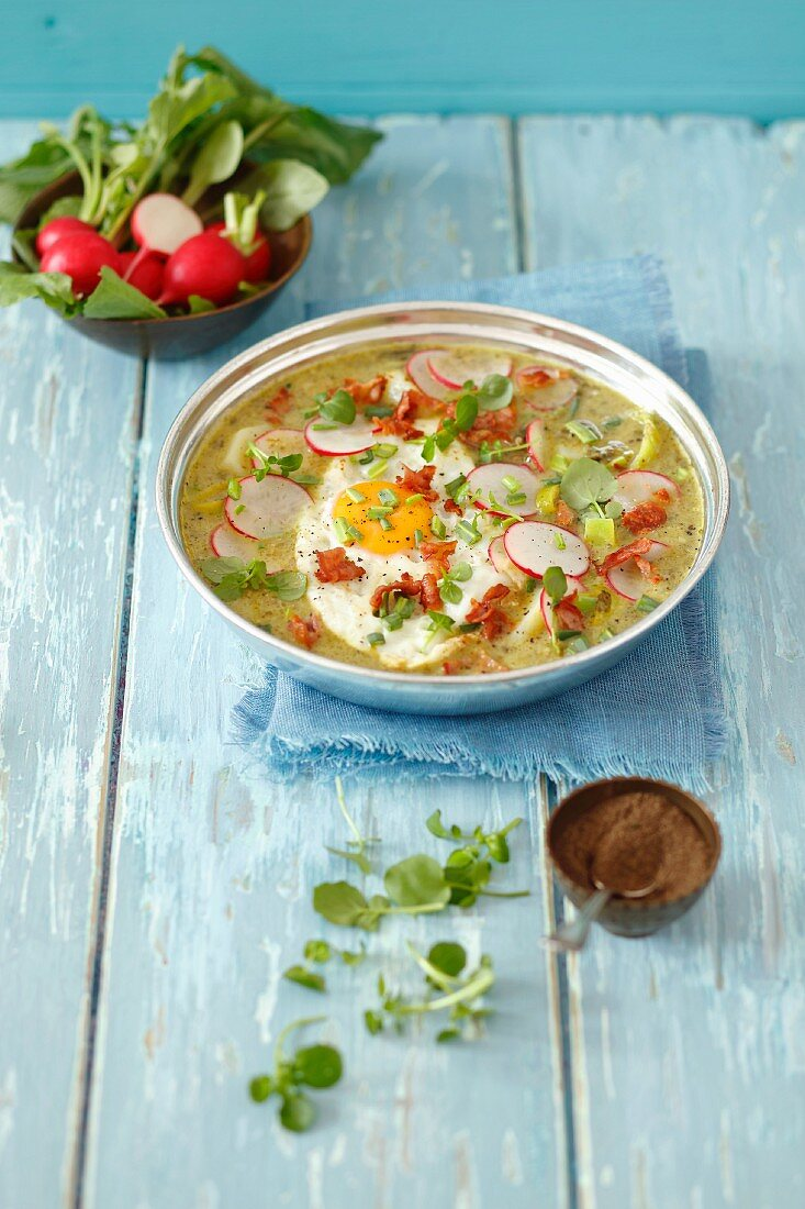 Sorrel and cress soup with potatoes, fried egg, bacon and red radishes