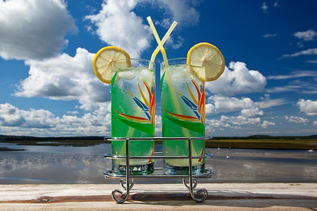Two glasses of lemonade by a river