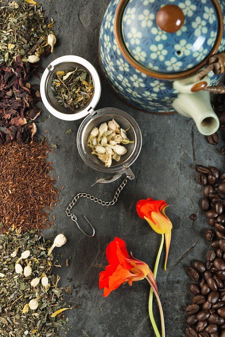 An arrangement featuring herbal tea, a teapot and coffee beans