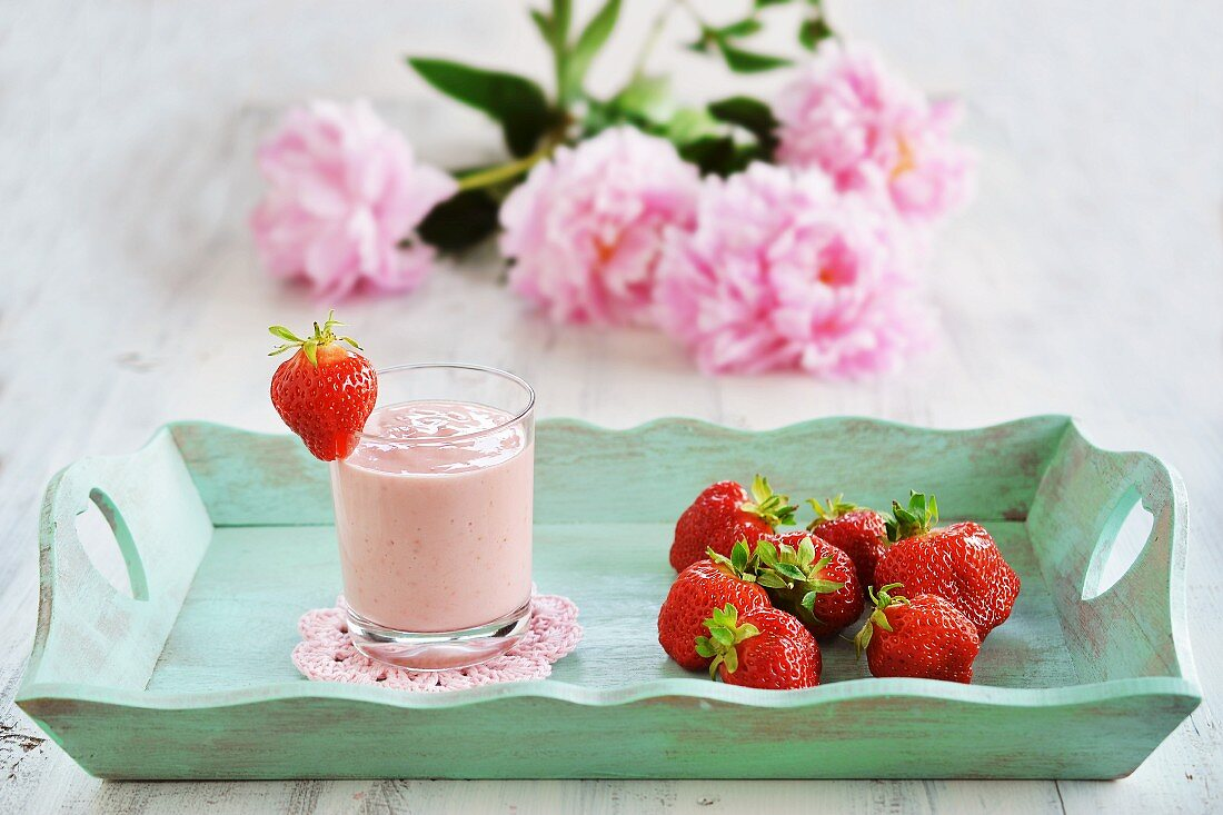 A glass of strawberry yoghurt and fresh strawberries on a wooden tray with a bunch of fresh summer flowers in the background