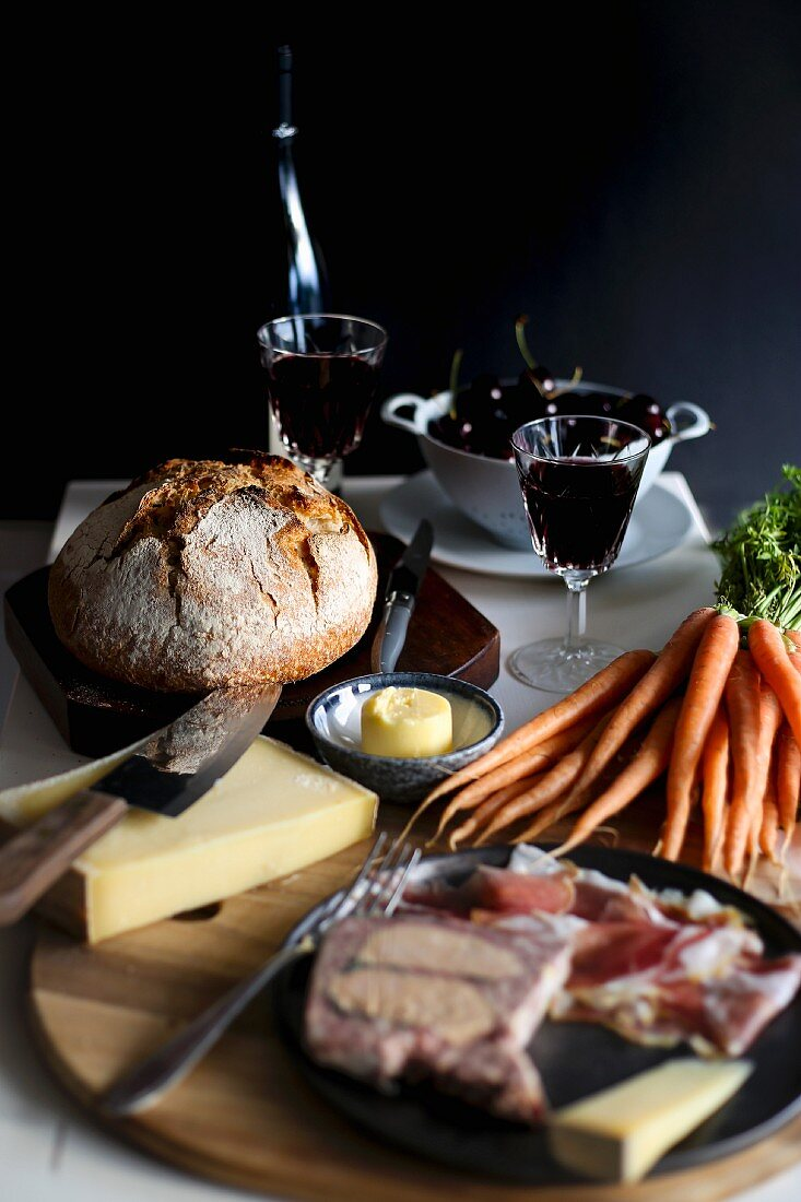 A set table with red wine, charcuterie, carrots, butter, cheese and bread