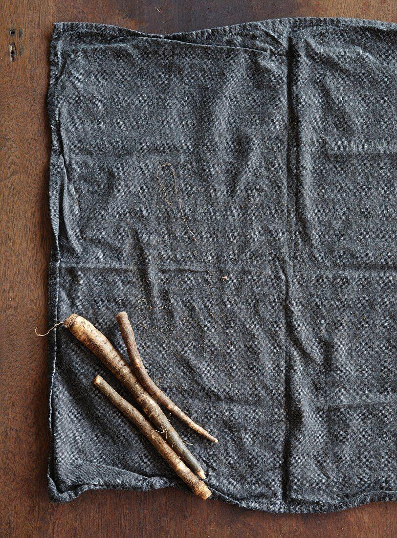 Drei frische Schwarzwurzeln auf Tuch liegend (Aufsicht)