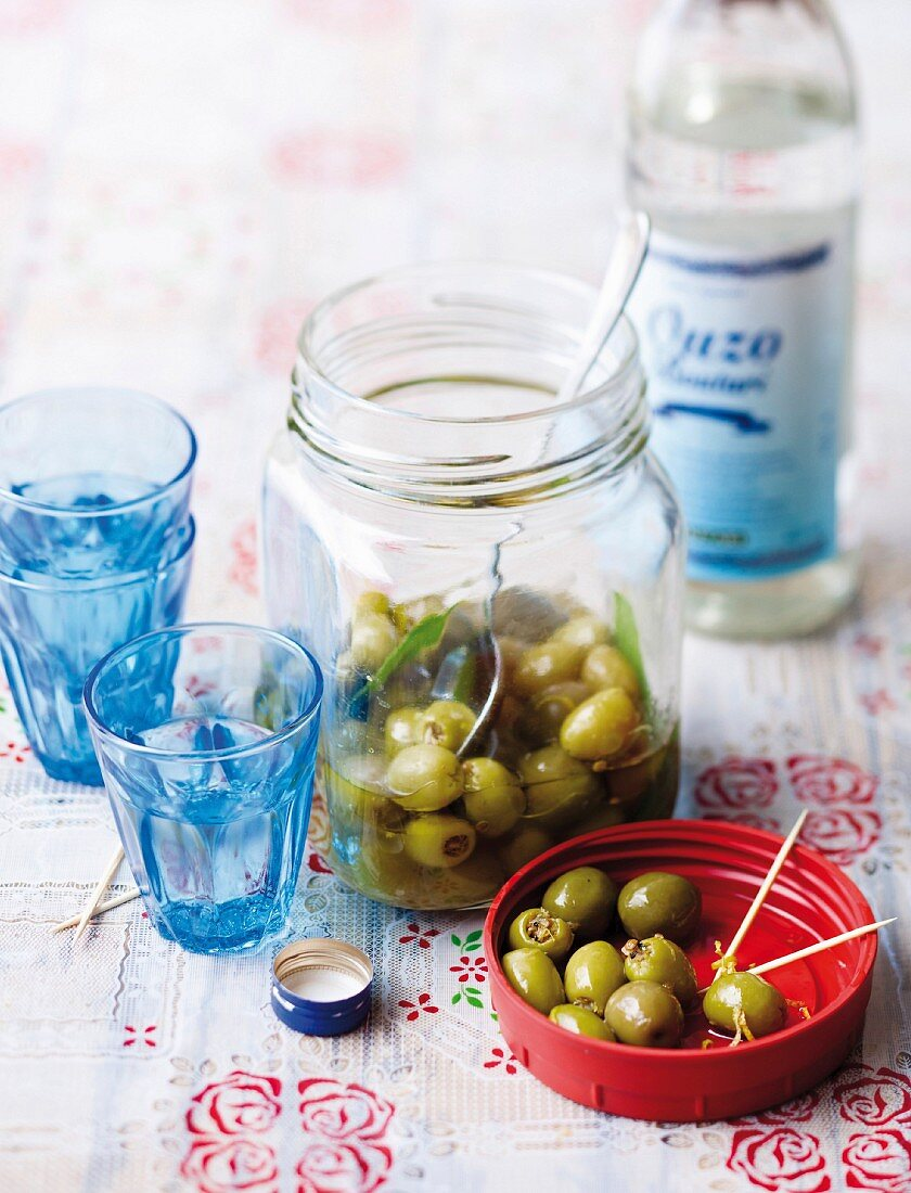 Olives with toothpicks and glasses of ouzo