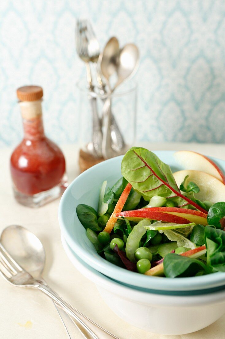 A mixed salad with apple slices, lime, peas and celery
