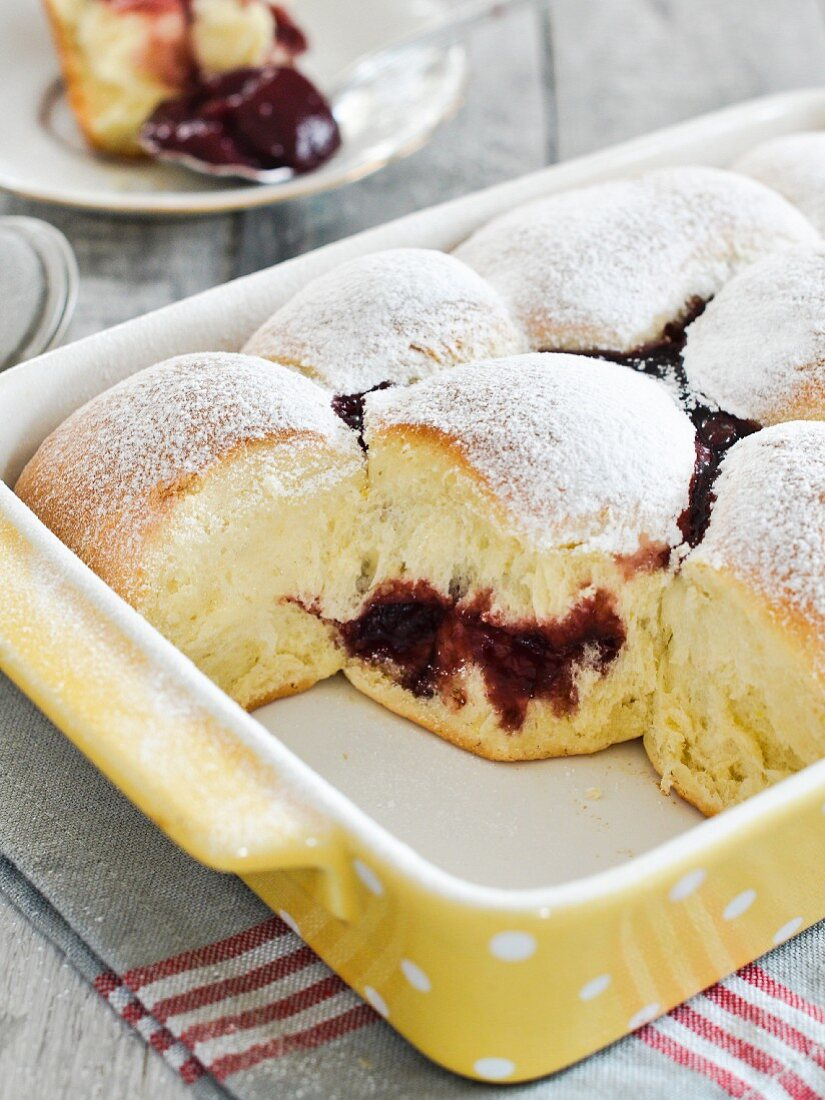 Baked sweet yeast dumplings with raspberry jam dusted with icing sugar