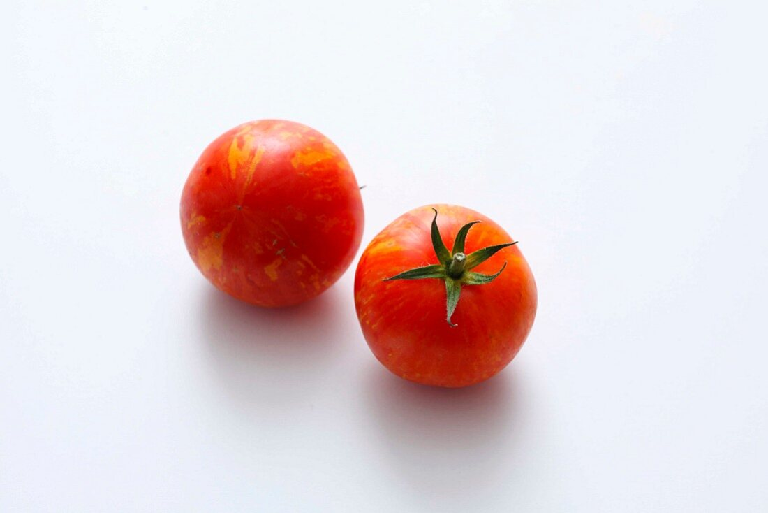 Two red striped tomatoes on a white surface