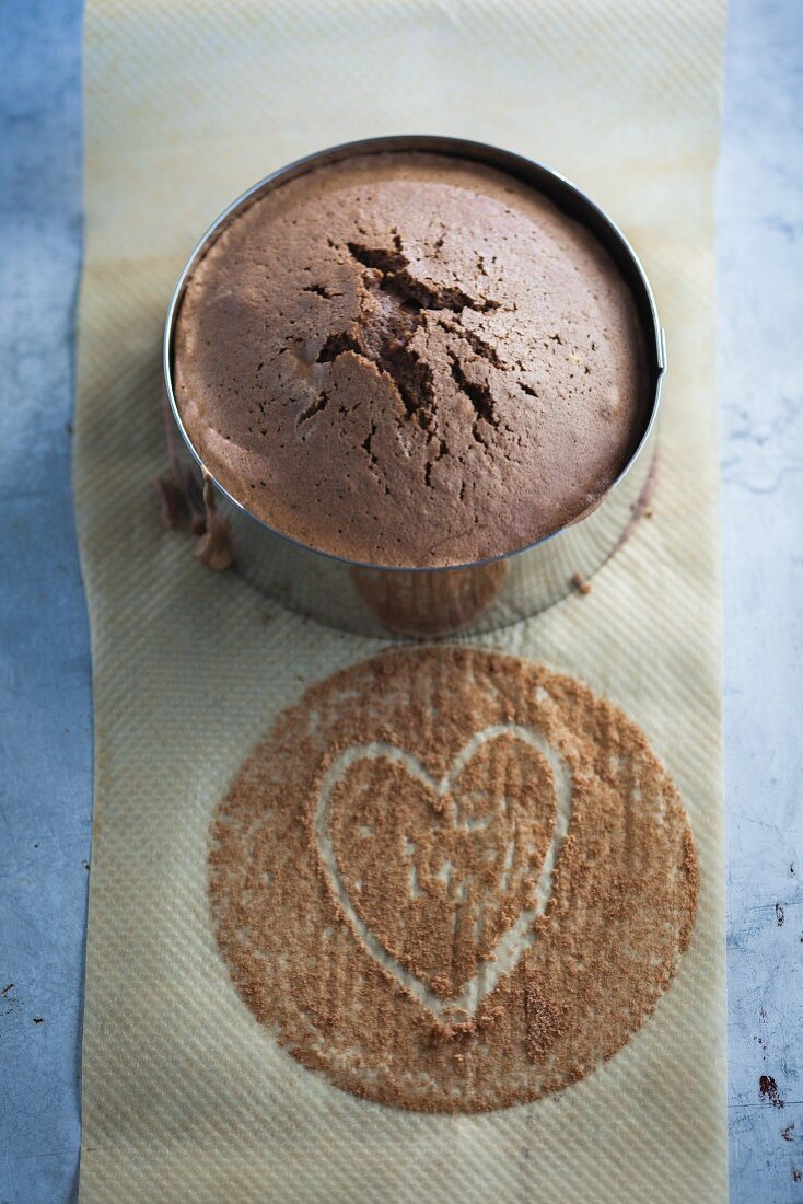 A chocolate cake in a baking tin with a heart drawn onto baking paper
