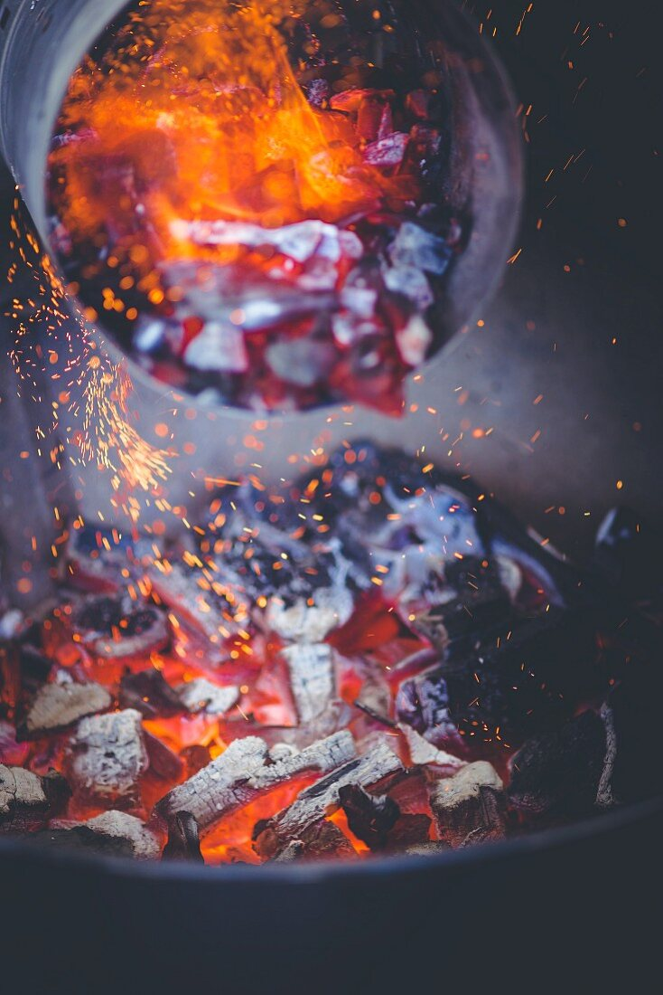 Glowing charcoal from a chimney starter being poured into a barbecue