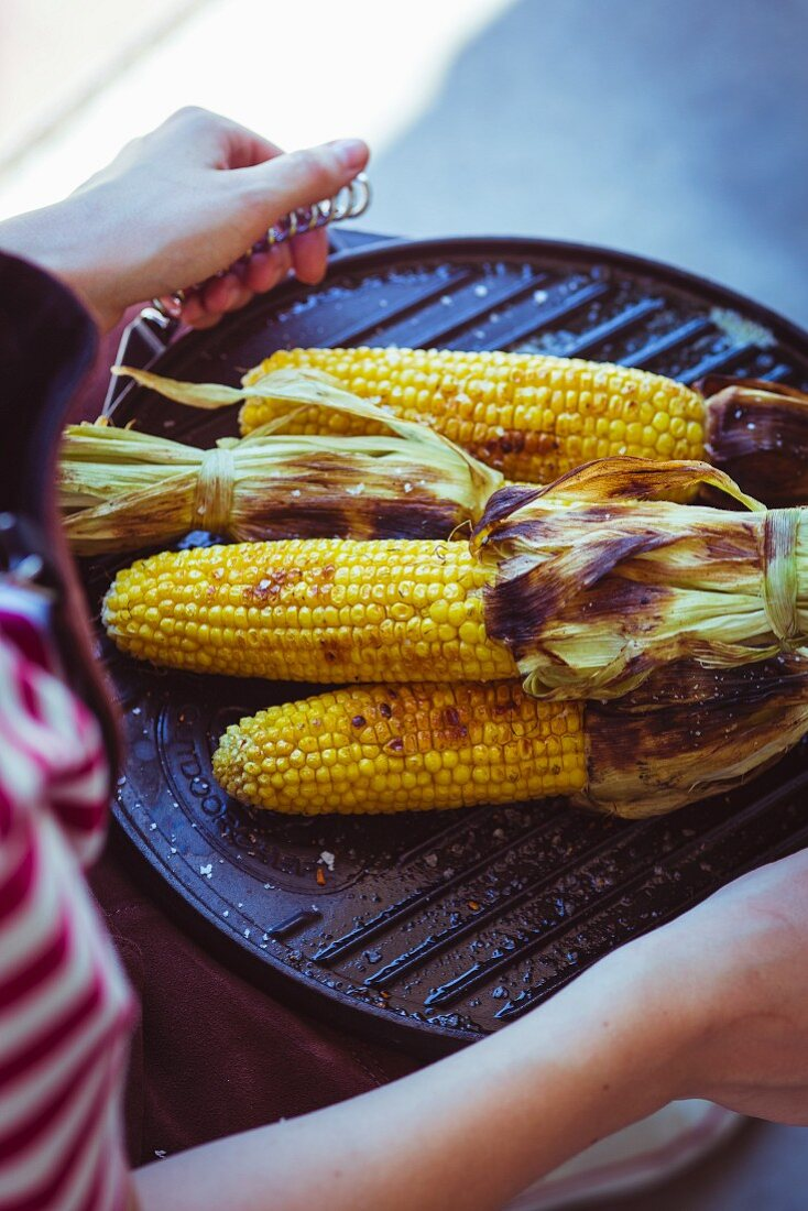 Grilled corn on the cob served on a barbecue griddle plate