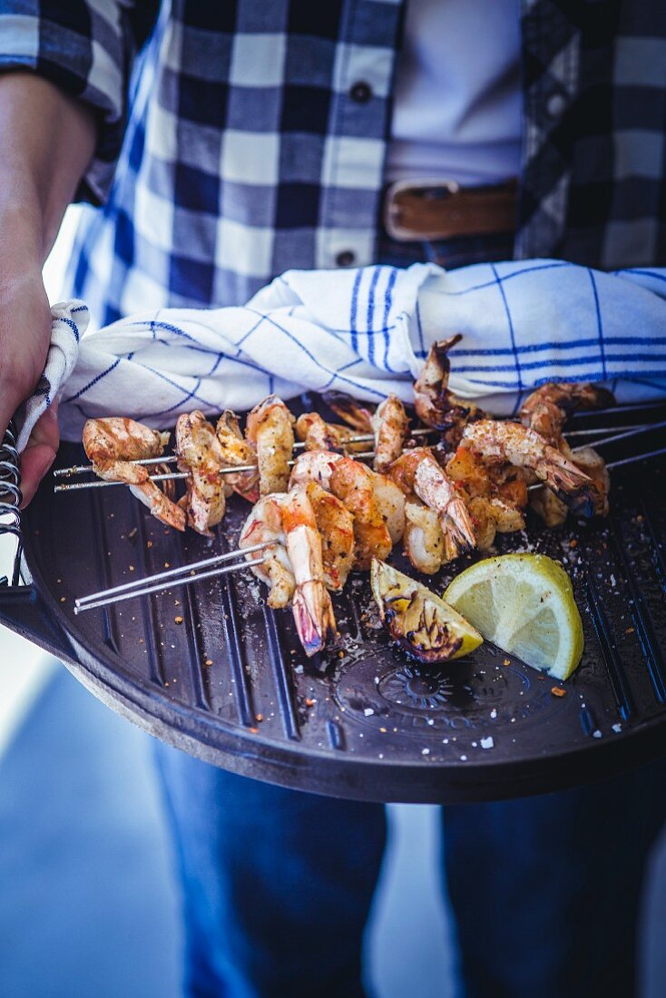 Grilled prawns skewers on a barbecue griddle plate