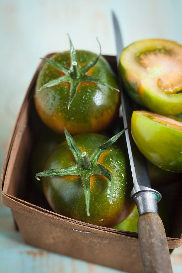 Green tomatoes with a knife in a basket
