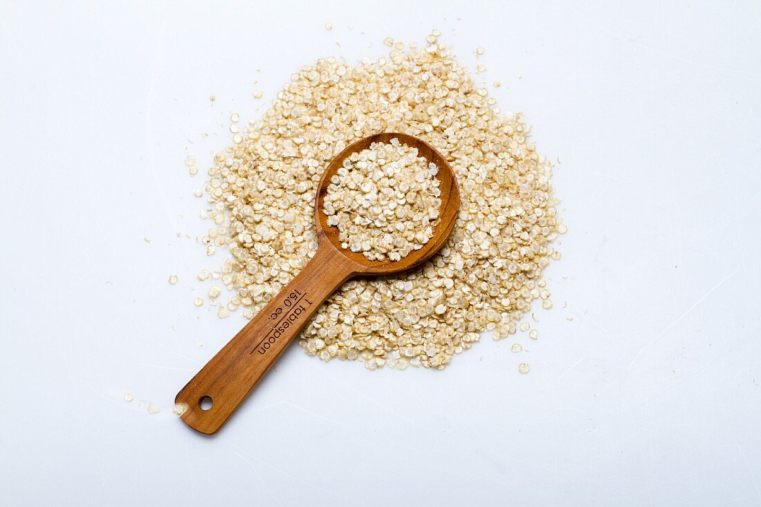 A pile of quinoa flakes with a wooden spoon on a white surface