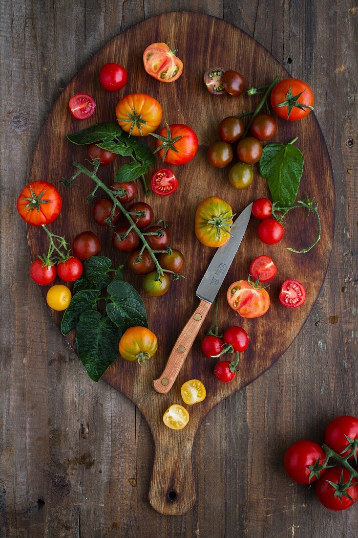 Various types of tomatoes on a wooden board (seen from above)