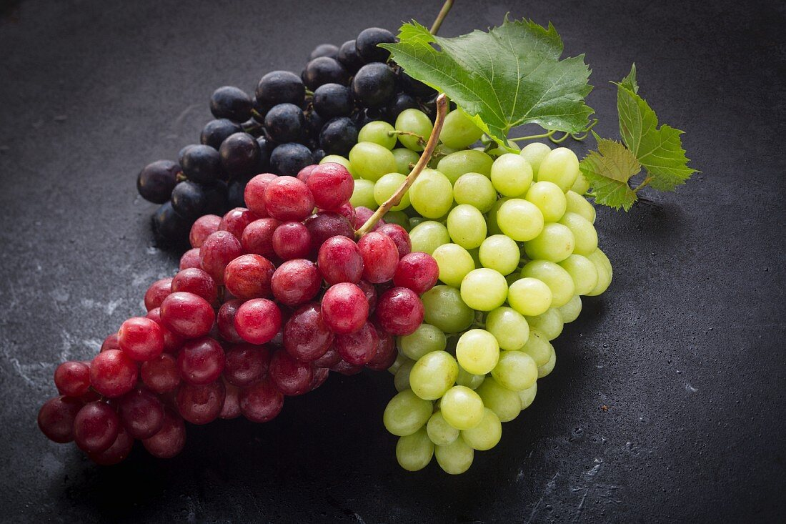 Black, red and green grapes on a black surface