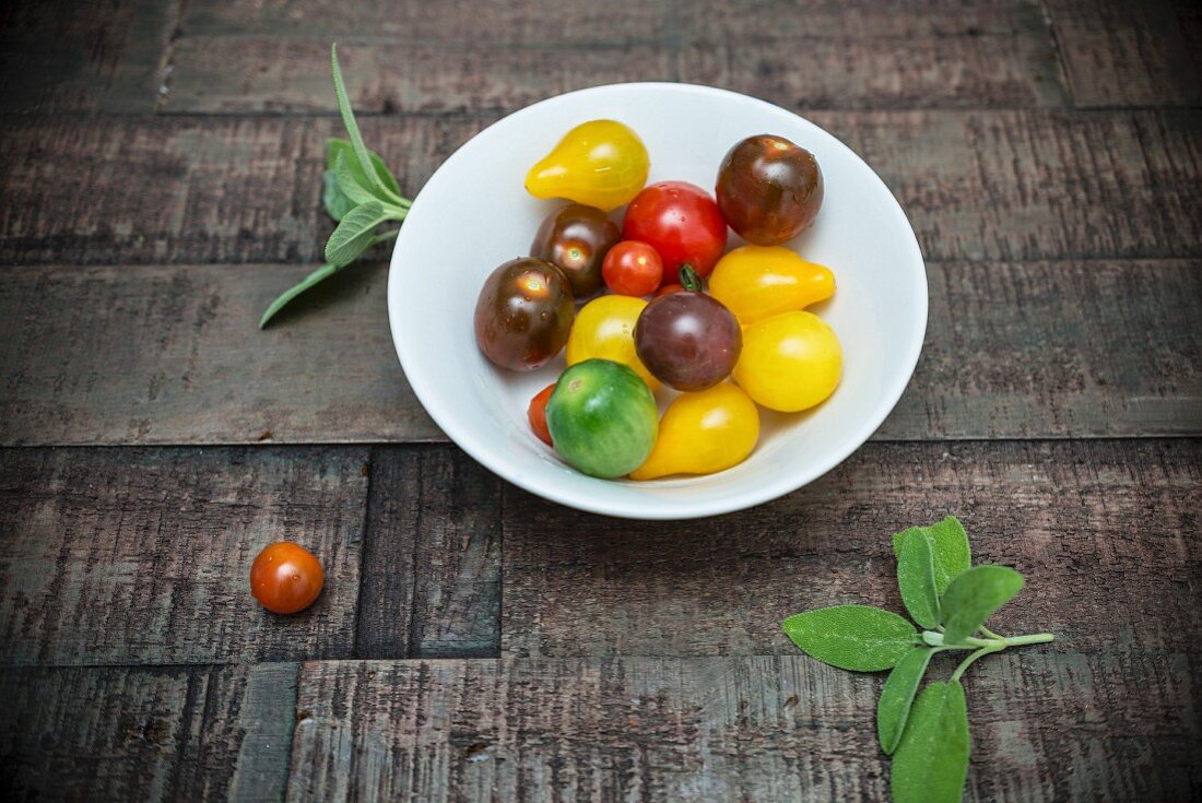 Various tomatoes in a porcelain bowl and fresh sage on a wooden surface