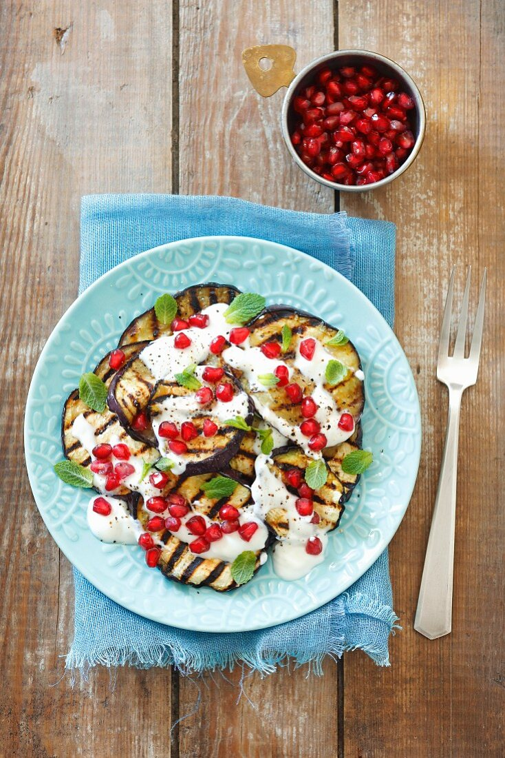 Grilled aubergine slices with yoghurt and pomegranate seeds