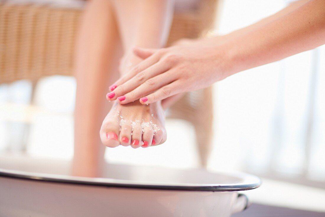 Frau nimmt Fußbad bekommt Meersalz-Peeling auf die Füße
