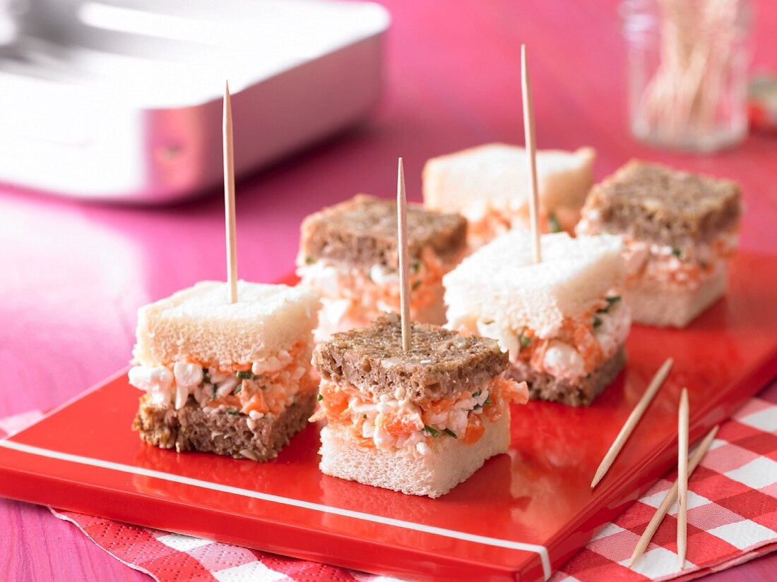 Brown and white sandwiches with cream cheese and carrots