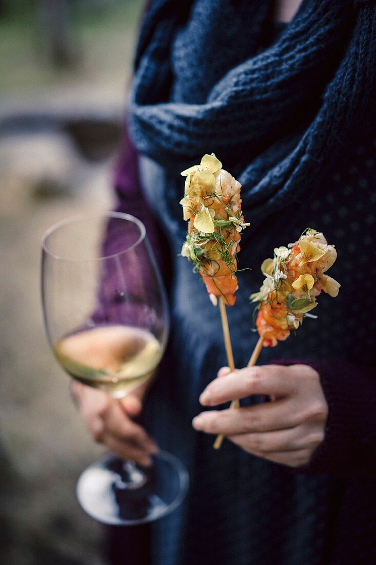 Grilled marron on a stick with citrus butter, flowers and herbs