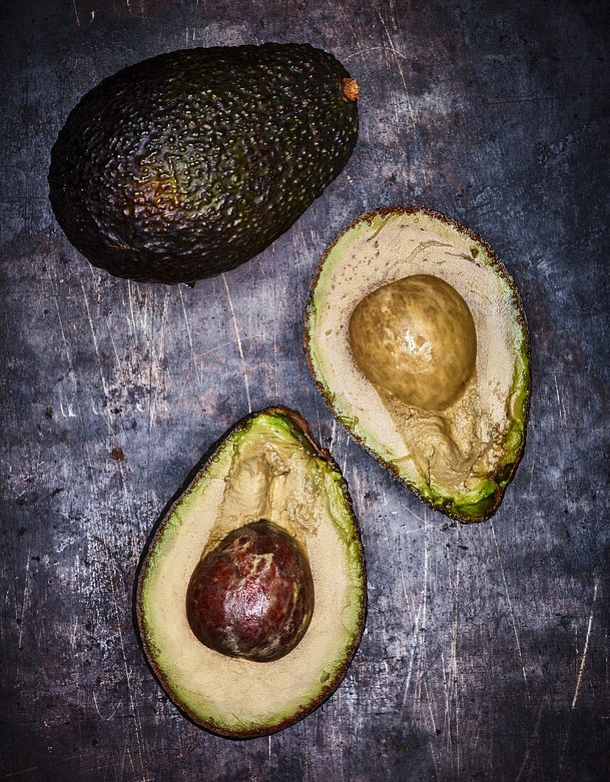A whole and a halved avocado on a grey surface (seen from above)