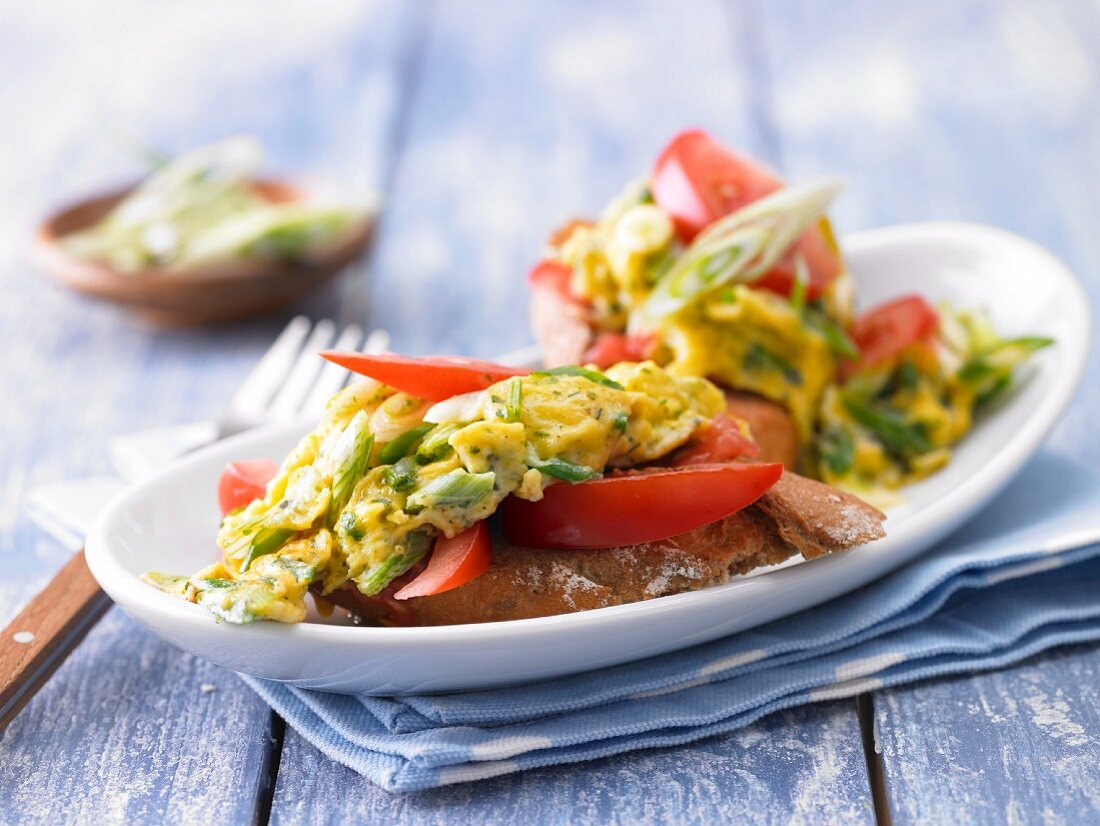 Scrambled egg with herbs on tomato baguette