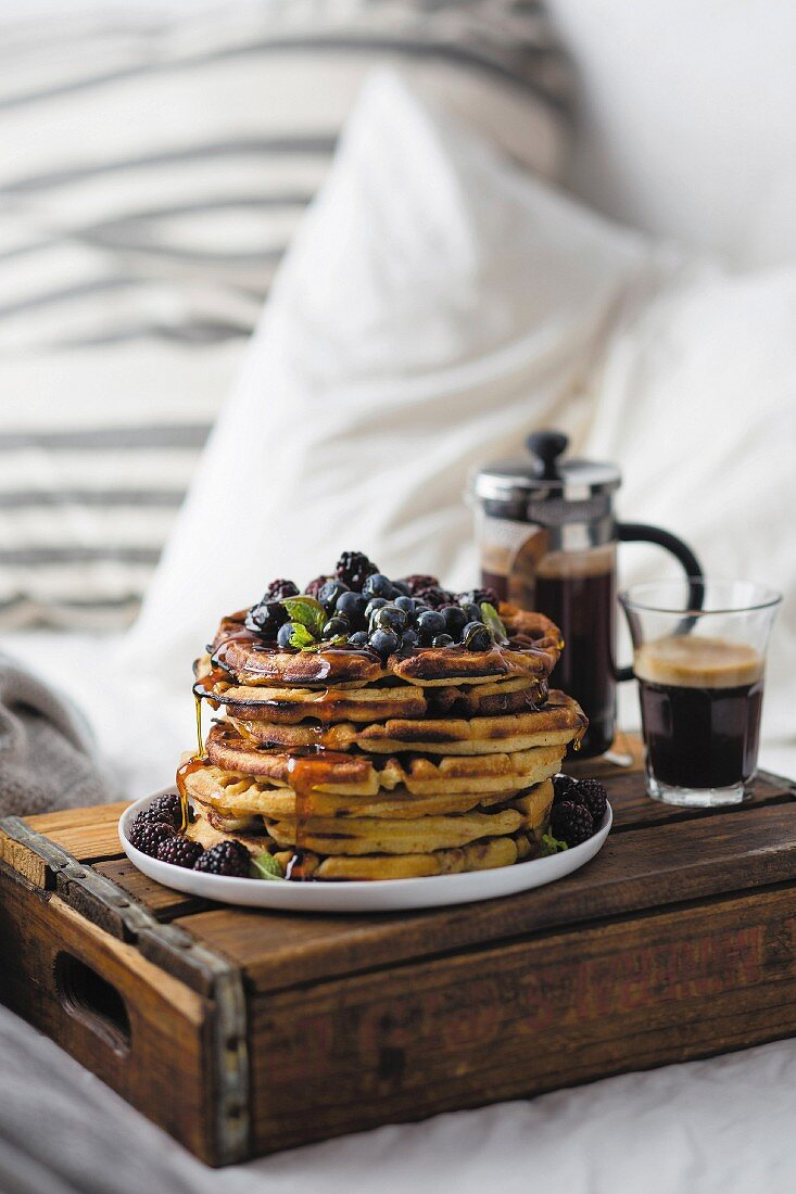 Breakfast in bed with waffles, berries and coffee
