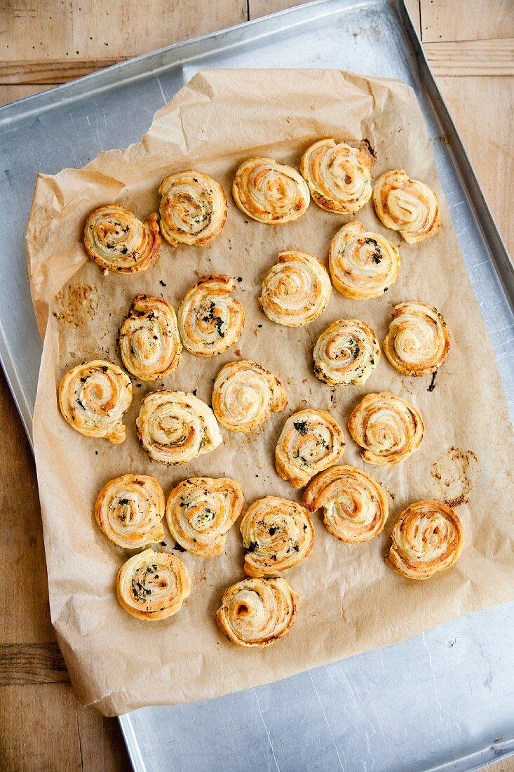 Freshly baked salmon puff pastry swirls on a baking sheet