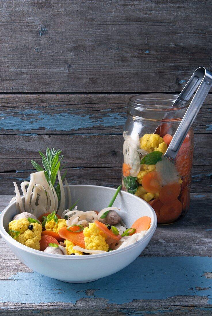 Pickled vegetables in a preserving jar and bowl