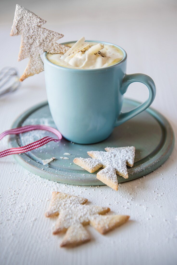 A mug of white hot chocolate with Christmas tree biscuits