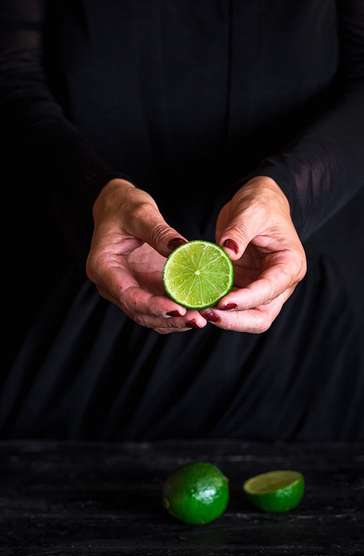 Half a lime in a woman's hands against a black background