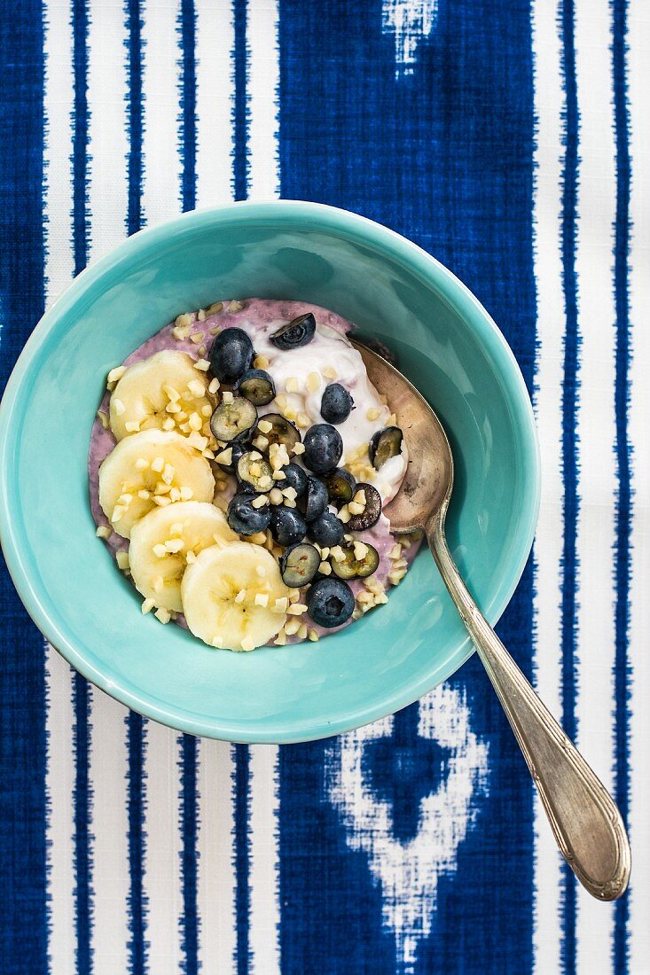 A bowl of muesli with banana and blueberries