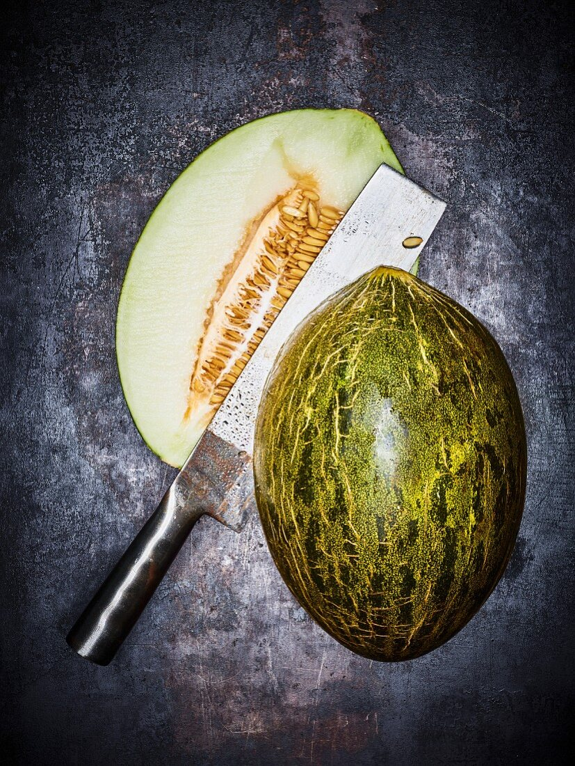 A Santa Claus melon (piel de sapo), cut in half, with a cleaver