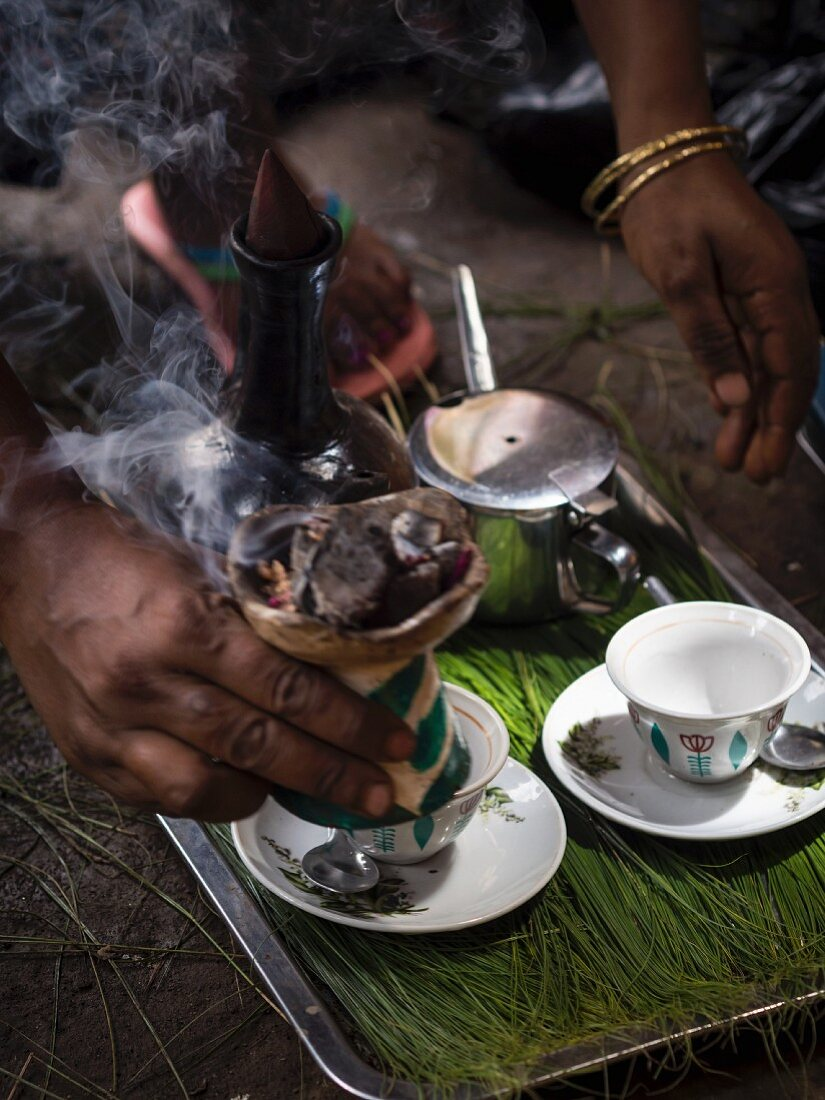 A woman preparing coffee during a traditional Ethiopian coffee ceremony