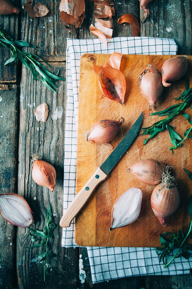 Shallots and tarragon with a knife on a chopping board